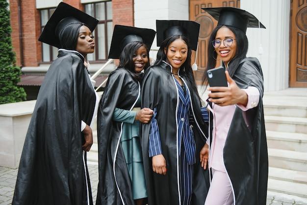 Onderwijs, afstuderen, technologie en mensen concept - groep gelukkige internationale studenten in mortelborden en vrijgezellenjurken met diploma's die selfie met smartphone buitenshuis nemen