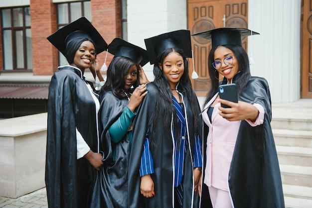 Onderwijs, afstuderen, technologie en mensen concept - groep gelukkige internationale studenten in mortelborden en vrijgezellenjurken met diploma's die selfie nemen door smartphone buitenshuis