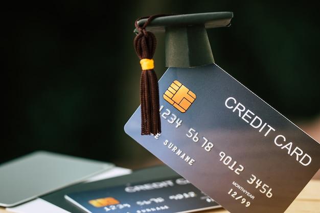 Onderwijs betaling credit card voor studie afgestudeerd concept: afstuderen cap op mock up card