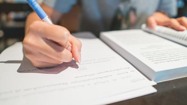 Onderwijs concept. close-up aan hand van de pen van de studentenholding en het schrijven op papier