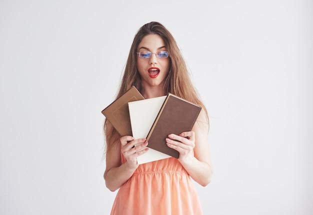 Onderwijs concept. foto van jonge vrouw in de glazen en rode lippen die de boeken houden.