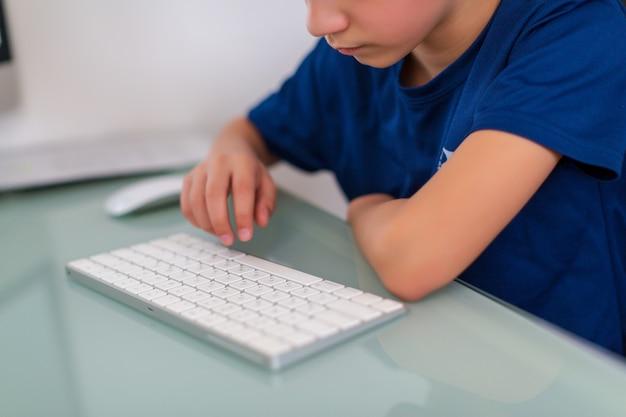 Onderwijs concept. kleine jongen te typen op het toetsenbord van de computer en zijn huiswerk op desktop-pc te werken