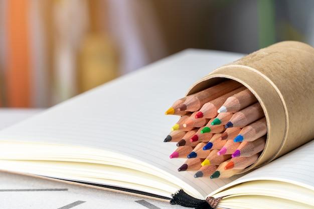 Onderwijs concept. kleurenpotloden in potloodhouder en boeken op witte lijst