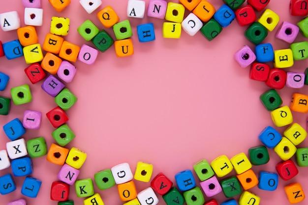 Onderwijs concept. kleurrijke blokken met letters op roze achtergrond. kopieer ruimte.