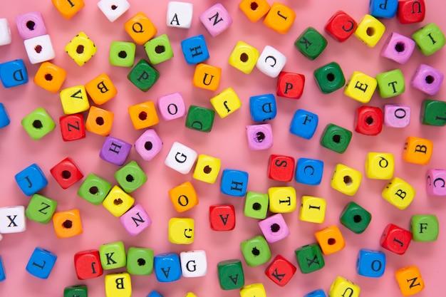 Onderwijs concept. kleurrijke blokken met letters op roze achtergrond. schrijfbericht.