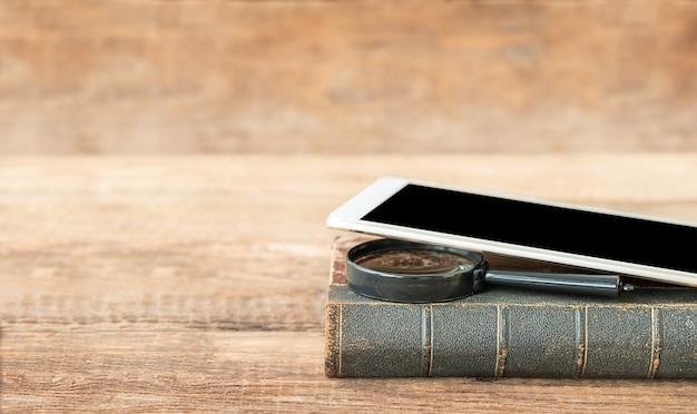 Onderwijs concept oude boek vergrootglas en tablet op een houten achtergrond en plaats voor tekst
