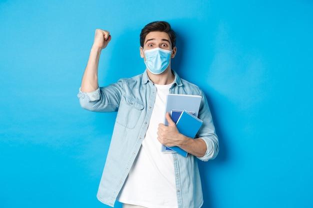Onderwijs, covid-19 en sociale afstand. opgewonden mannelijke student met medisch masker triomfeert, steekt vuist op en houdt notitieboekjes vast, staande over blauwe achtergrond.