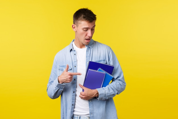 Onderwijs, cursussen en universitair concept. knappe jonge mannelijke student wijzende vinger naar notebooks en studiemateriaal, huiswerk voorbereiden op college opdracht, gele achtergrond.