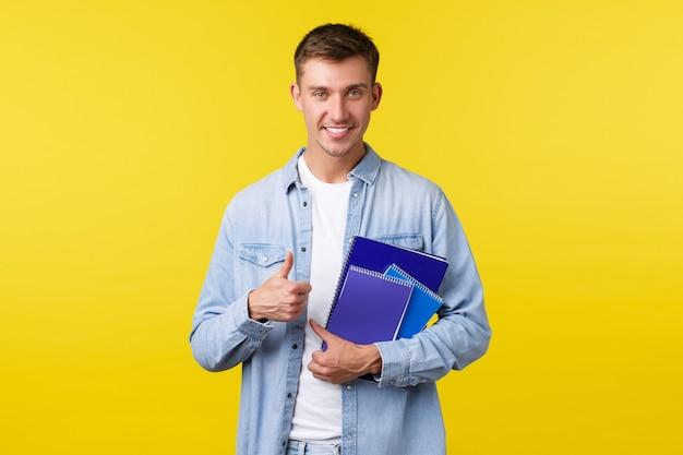 Onderwijs, cursussen en universitair concept. knappe slimme mannelijke student, gelukkig glimlachend en duimen omhoog, draagt studiemateriaal en notebooks, genietend van het leven op de campus, gele achtergrond.
