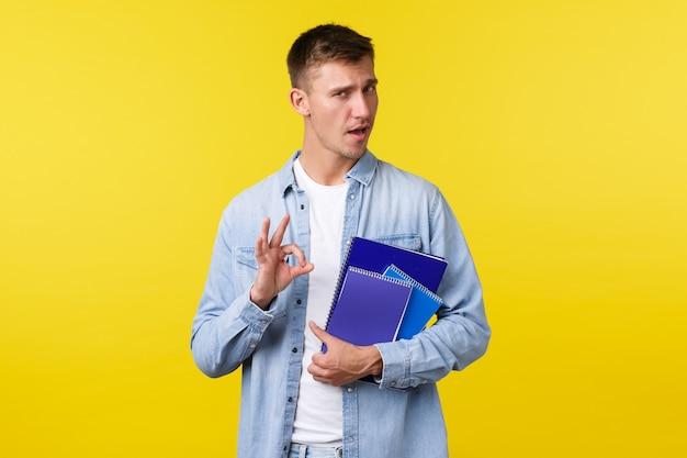 Onderwijs, cursussen en universitair concept. knappe, zelfverzekerde blonde man moedigt aan om deze universiteit in te schrijven, een goed gebaar te tonen als garantie dat je het leuk zult vinden, met notitieboekjes, gele achtergrond.