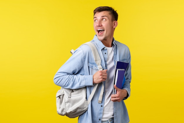 Onderwijs, cursussen en universitair concept. opgewonden, gelukkig lachende knappe student keert terug naar de linkerbovenhoek terwijl hij op weg is naar lessen met rugzak en notebooks, gele achtergrond.