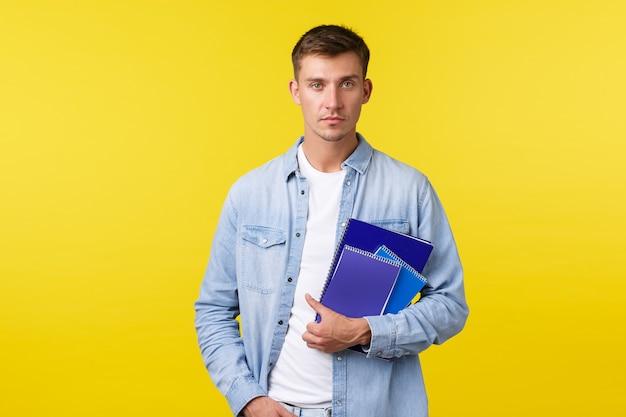 Onderwijs, cursussen en universitair concept. serieus uitziende student, man met notitieboekjes, vastberaden camera, nonchalante uitdrukking als op weg naar de klas, gele achtergrond.