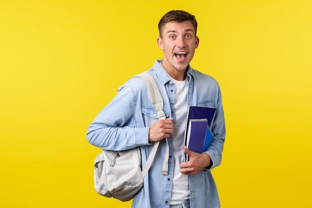 Onderwijs, cursussen en universitair concept. verrast, gelukkig lachende man die iets verbaasd ziet terwijl hij naar de klas gaat op de universiteit of kostschool, met een rugzak met notitieboekjes.