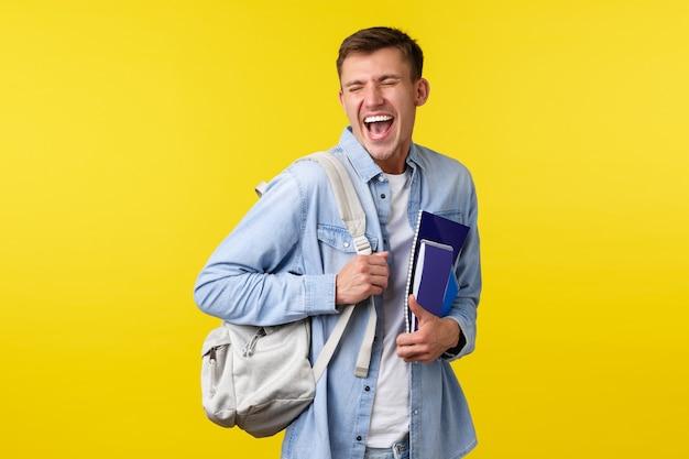 Onderwijs, cursussen en universitair concept. vrolijke gelukkige knappe mannelijke student die geniet van het leven op de campus, rugzak en studiemateriaal vasthoudt, lachend en glimlachend opgewonden, gele achtergrond.