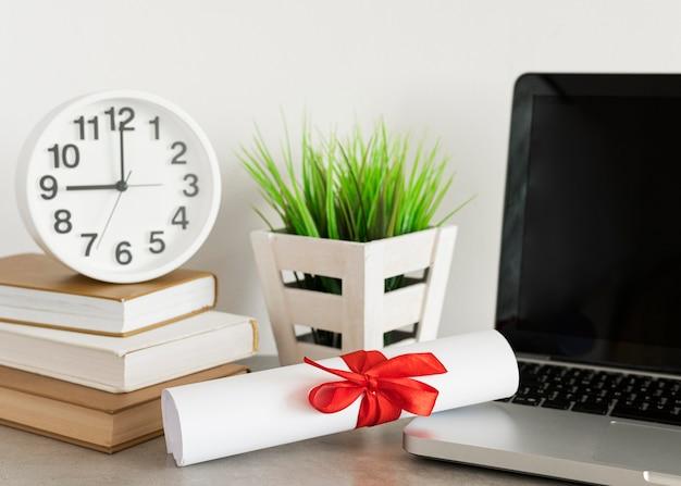 Onderwijs diploma certificaat opgerold en laptop