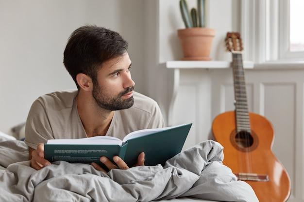 Onderwijs en examenvoorbereiding concept. ongeschoren jongeman ligt in bed, houdt boek vast