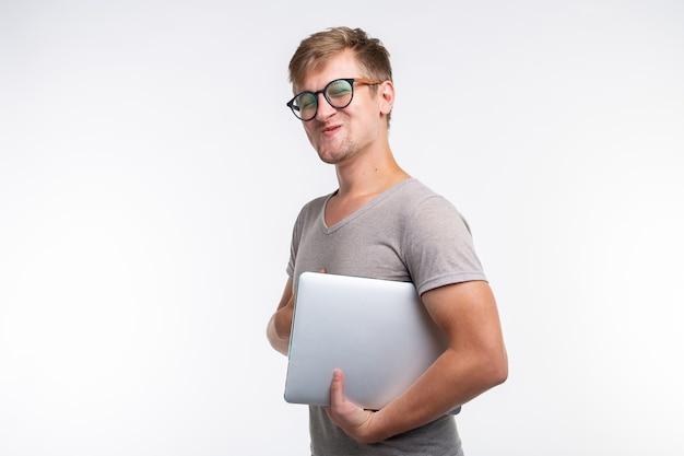 Onderwijs en mensen concept. knappe student man met bril ziet eruit als blij met laptop.