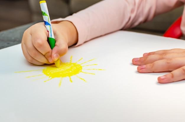 Onderwijs en school. onderwijs en kleuterschool concept. schattig klein meisje tekent de zon met potloden