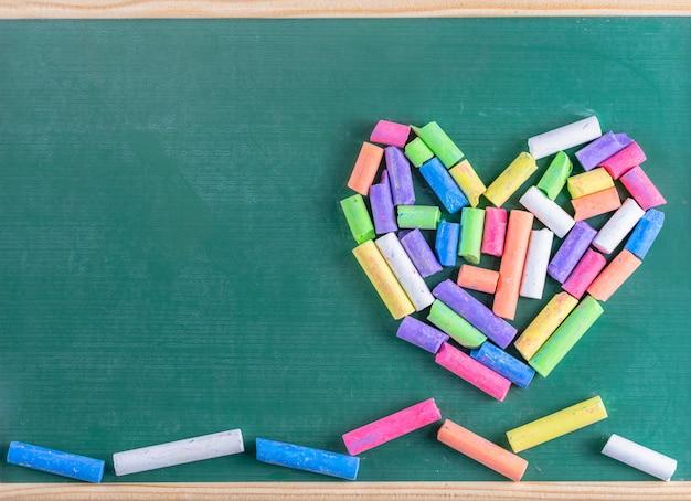 Onderwijs en schoolconcept, kleurenkrijt op groen bord
