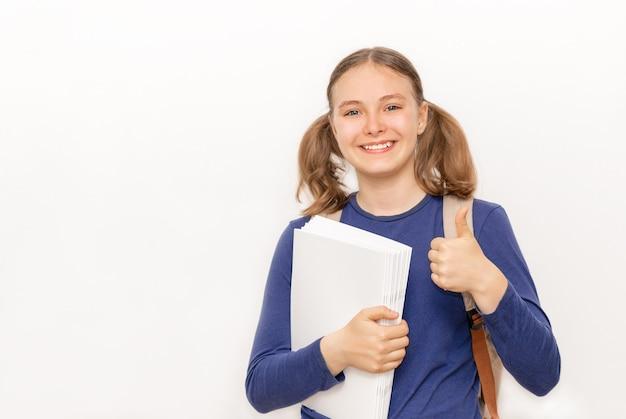 Onderwijs en terug naar school concept glimlachend schoolmeisje met voorbeeldenboeken op de grijze achtergrond