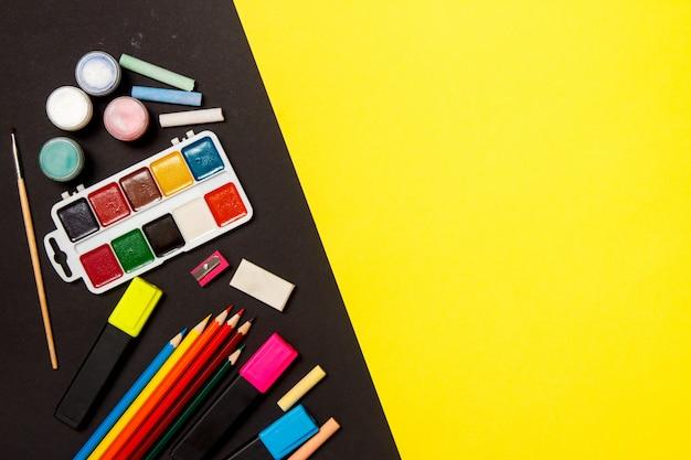 Onderwijs en terug naar school-concept. schoollevering voor het trekken op een gele achtergrond. bovenaanzicht, plat leggen.