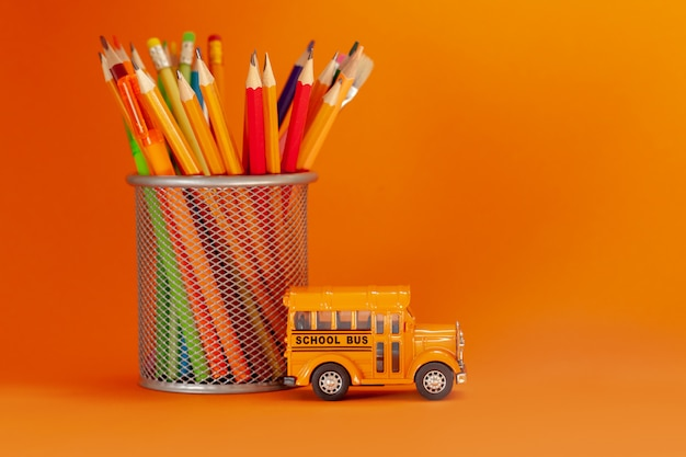 Onderwijs en terug naar schoolconcept. gele retro schoolbus en potloden in mand op sinaasappel