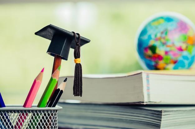 Onderwijs gediplomeerd studieconcept: zwarte graduatiehoed op potloden, de aarde van onduidelijk beeldeuropa