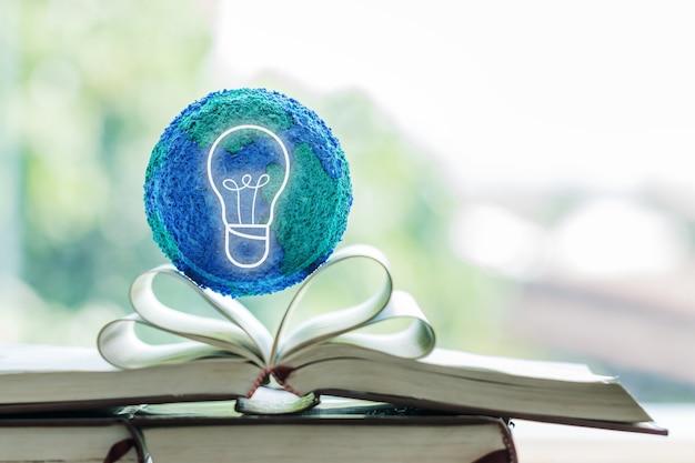 Onderwijs in toekomstig creatief leren onderzoek naar internationale onderwijsprojecten. open leerboek met bolmodel met gloeilamp. concept van het lezen of denken van innovatie voor kennis op de universiteit