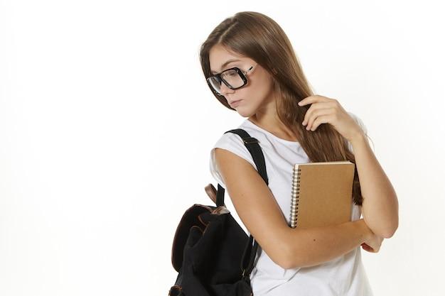 Onderwijs, kennis en leerconcept. stijlvol schoolmeisje in brillen die met rugzak naar school gaan. mooie schattige vrouwelijke student schoudertas en leerboek, poseren
