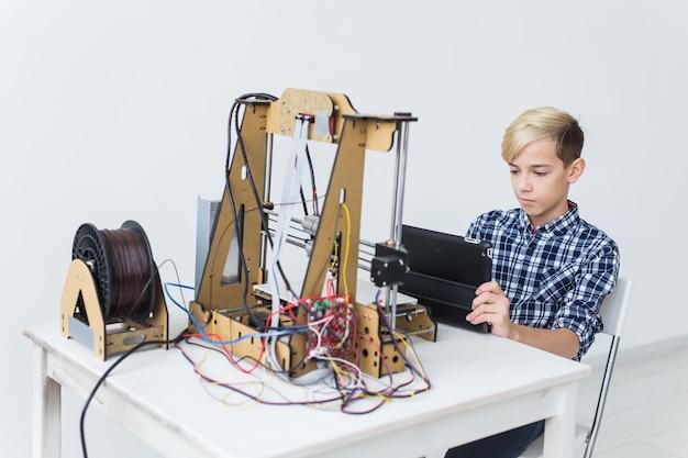 Onderwijs, kinderen, technologieconcept. tienerjongen drukt af op 3d-printer.