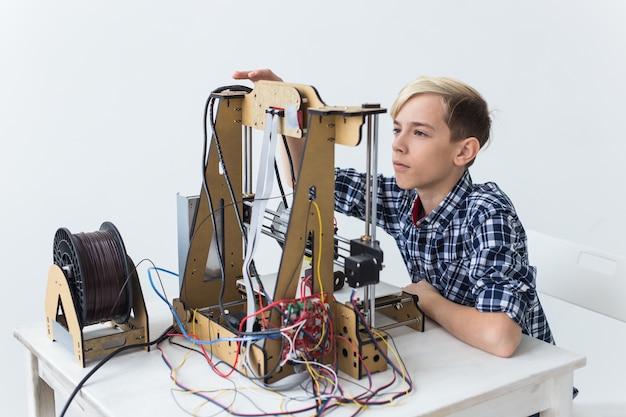 Onderwijs, kinderen, technologieconcept - tienerjongen drukt op 3d-printer af.