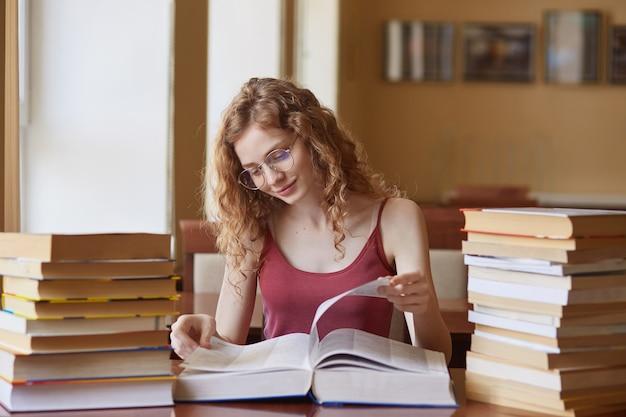 Onderwijs, middelbare school, universiteit, leren en mensen concept. binnenschot van de lezingsboek van het studentenmeisje bij bibliotheek, voorbereidend op test, die nuttige informatie, wijfje met foxy haar te weten komen.