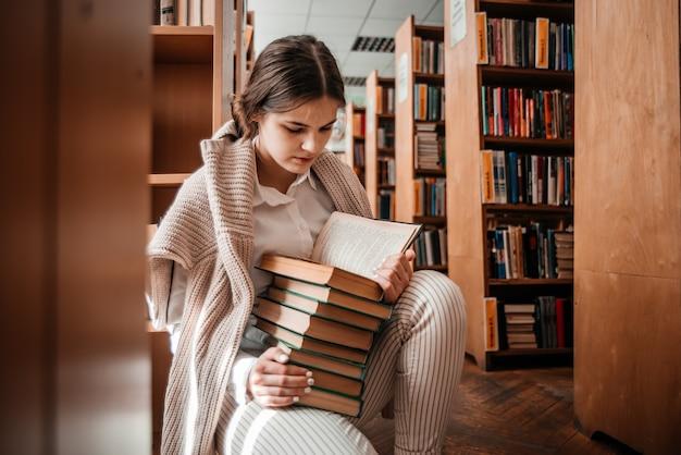 Onderwijs, middelbare school, universiteit, leren en mensen concept - glimlachend studentenmeisje leesboek bij bibliotheek