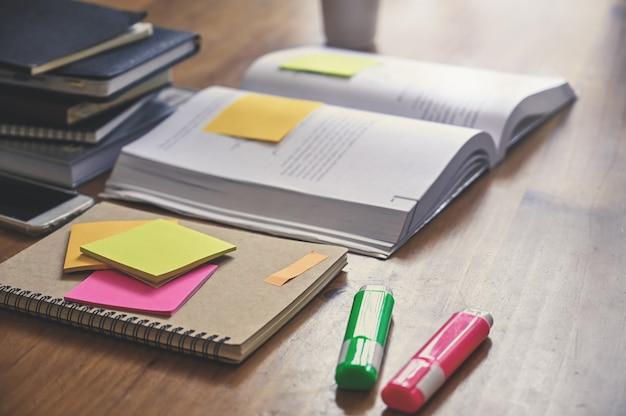 Onderwijs, notebook, boek met notitie op houten tafel.
