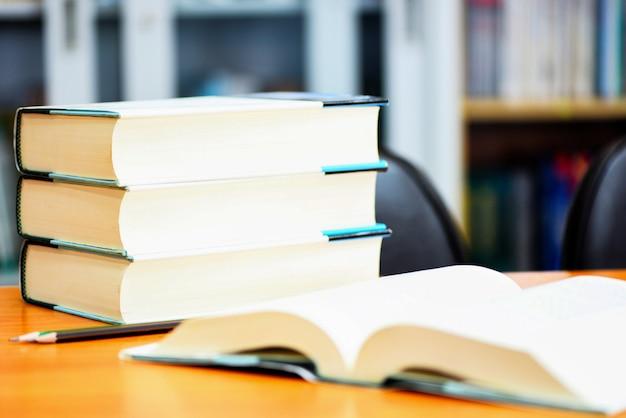 Onderwijs of terug naar school en studeer open boek in bibliotheek met boek dat op lijst wordt gestapeld