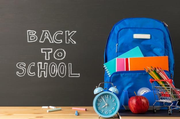 Onderwijs of terug naar schoolconcept, rugzak en kantoorbehoeftenlevering op klaslokaalbureau met bordachtergrond.