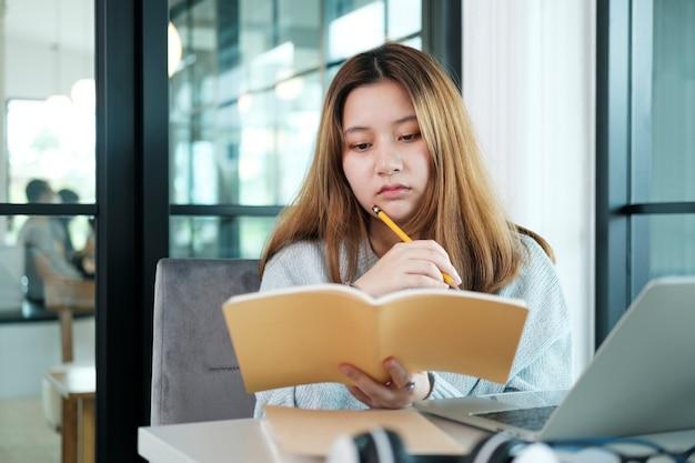 Onderwijs online leren of zelfstudie concept. collagemeisje onderzoekt en vindt online uit boeken en internet.