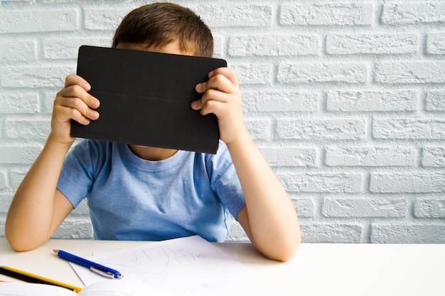 Onderwijs op afstand. jongen gebruikt een laptop en verstopt zich erachter. thuisonderwijs, leren op afstand, online onderwijs, videogesprek