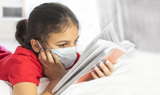 Onderwijs op afstand, online onderwijs leren. meisje dat masker draagt, dat thuis bestudeert
