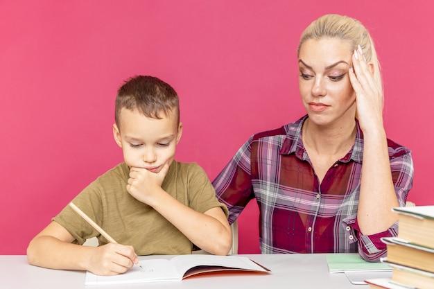 Onderwijs op afstand. thuisonderwijs voor kinderen. moeder helpt zoon om te leren.