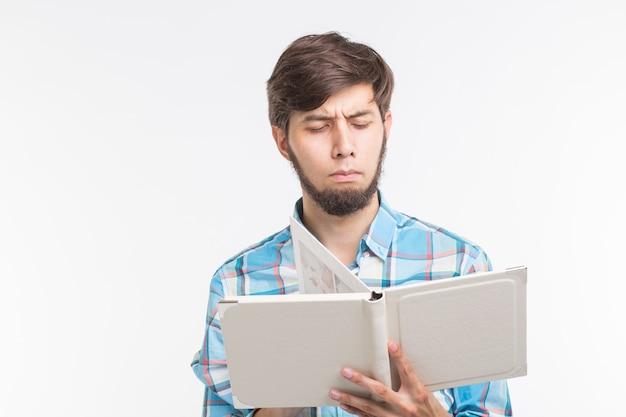 Onderwijs, proces en mensen concept - jonge man serieus lezen van een boek.