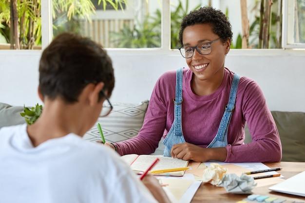 Onderwijs, relatie en samenwerkingsconcept. tevreden zwarte jonge vrouw met krullend haar, draagt een bril voor correctie van het gezichtsvermogen, kijkt positief naar leerling die materiaal probeert te begrijpen