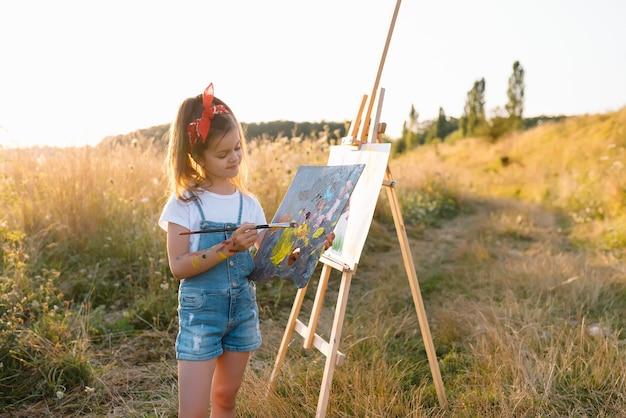 Onderwijs, school, kunst en painitng concept - klein student meisje schilderij beeld