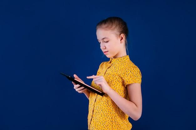Onderwijs, school, technologie en internet concept - klein studentenmeisje met tablet pc op school