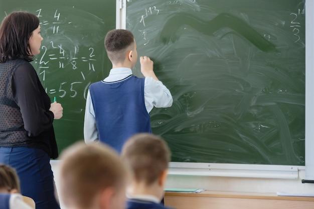Onderwijs. schoolkind en leraar schrijven op het bord in de klas in de klas. opleiding, kinderopvang. achteraanzicht. geselecteerde focus.