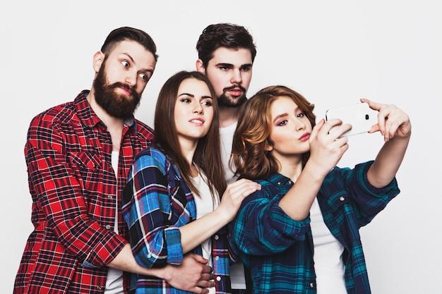 Onderwijs, technologie en mensen concept: groep studenten nemen selfie met smartphone op witte achtergrond. speciale modieuze toning.