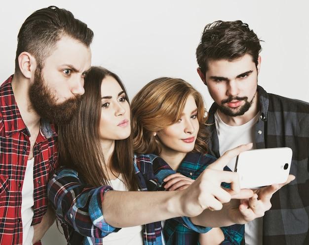 Onderwijs, technologie en mensen concept: groep studenten selfie met smartphone nemen over witte ruimte.speciale modieuze toning.