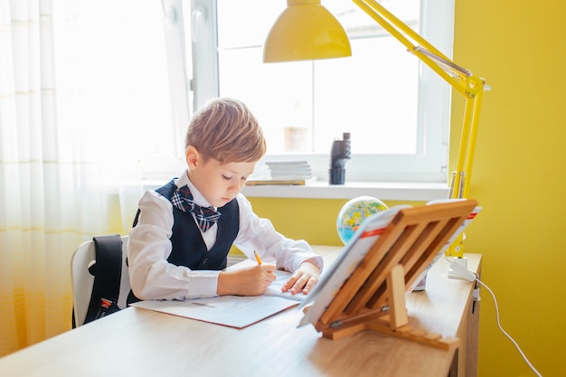 Onderwijs thuis concept - leuk weinig jongen die of het huiswerk aan studielijst bestuderen voltooien met stapel van boeken, onderwijsbol en werkboek