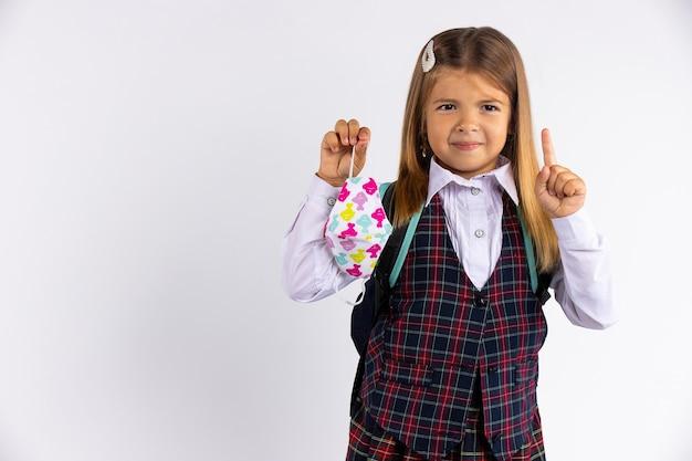 Onderwijs tijdens quarantainecovid. kindmeisje in uniform wijst vinger naar de zijkant, geïsoleerd op grijze muur.