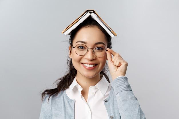 Onderwijs, universiteit en mensenconcept. blijf thuis en studeer op afstand. vrolijke aziatische vrouw in glazen, boek of planner op haar hoofd houden, studeren, voorbereiden op tests na quarantaine eindigt